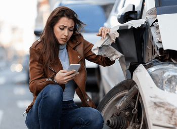Woman on her cell phone and kneeling beside her car that has been in a bad wreck