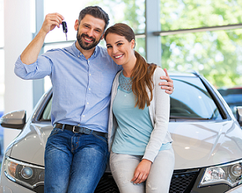 Couple posing in from of new car at dealership the man has a car key held up in his hand and his other arm around his wife
